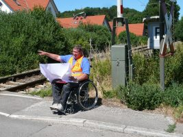 Maximilian Geier im Rollstuhl an Bahnübergang mit Plan in der Hand