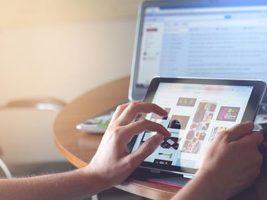 Zwei Hände berühren den Touchscreen eines Tablets